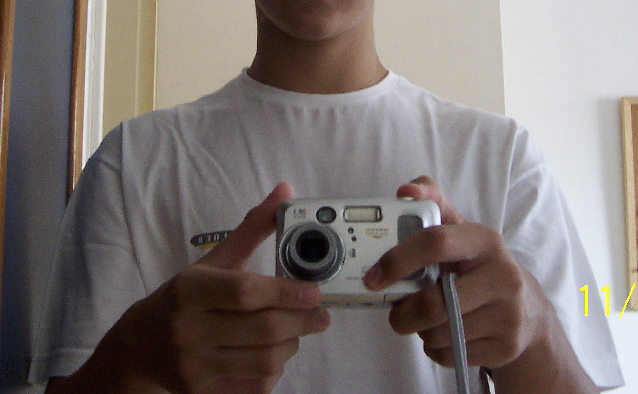Hands holding an old digital camera, the CX6330, taking a photo of a mirror where the camera appears
